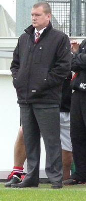 Karl Marginson, F.C. United's longest serving manager, stands at the side of a football pitch watching the game.