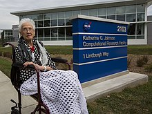 Johnson seated on a bench beside a sign in front of the Katherine G. Johnson Computational Research Facility.