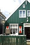 foto van Perceelsgedeelte van een houten huis met aan de straatzijde een bakstenen pui waarin eenvoudig snijraam. Daklijst op consoles