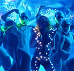 A blond woman dancing in a blue dress, which has small glowing lights on it. She is surrounded by dancers in silver, body-hugging dress with a neon green mask in front