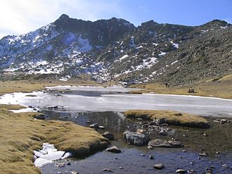 Peñalara Natural Park - Bird Lake and the Cliff of Carnations and Bird Cliff behind.  The Cliff of Carnations is the second-highest peak in the Sierra de Guadarrama.