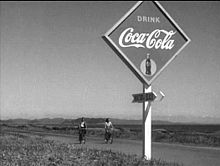 A young Japanese man and woman, both in casual clothes, are riding bicycles over a paved road in the near background of the image; mountains are visible in the far distance. In the foreground of the image, at the edge of the road, is a diamond-shaped Coca-Cola sign, below which is an arrow upon which is written the name (in English) of a beach.