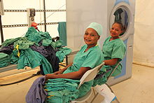Two women with large piles of scrubs and a washing machine