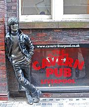 Statuo prezentante junan Lennon ekster brikdomo. Plej proksime al la statuo estas tri fenestroj, kun du flank-al-flankaj super la pli malalta, kiu portas signaĝon reklamantan la Cavern-drinkejon.