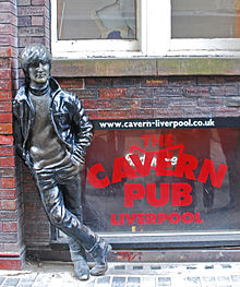 A statue depicting a young Lennon outside a brick building. Next to the statue are three windows, with two side-by-side above the lower, which bears signage advertising the Cavern pub.