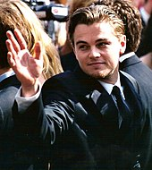 A picture of Leonardo DiCaprio with his hand raised.