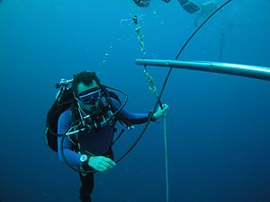 Diving shot - Scuba diver decompressing on decompression trapeze shotline using surface supplied gas