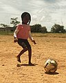 Little Zambian girl playing football.jpg