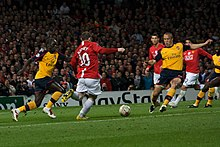 Wayne Rooney (in red) is shaping to kick the ball with an Arsenal player (in yellow) on either side of him. Cristiano Ronaldo, Carlos Tévez (both Manchester United) and Kolo Touré (Arsenal) are looking on in the background.