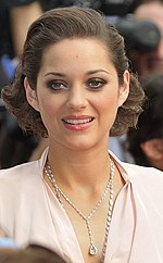 Headshot of a brown-haired French female wearing a silver necklace and a pink dress.