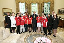 Fourteen people stand in a line, seven of whom are wearing medals and red T-shirts, and the other seven of whom are dressed formally.