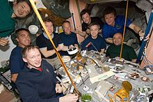 Thirteen astronauts seated around a table covered in open cans of food strapped down to the table. In the background a selection of equipment is visible, as well as the salmon-coloured walls of the Unity node.