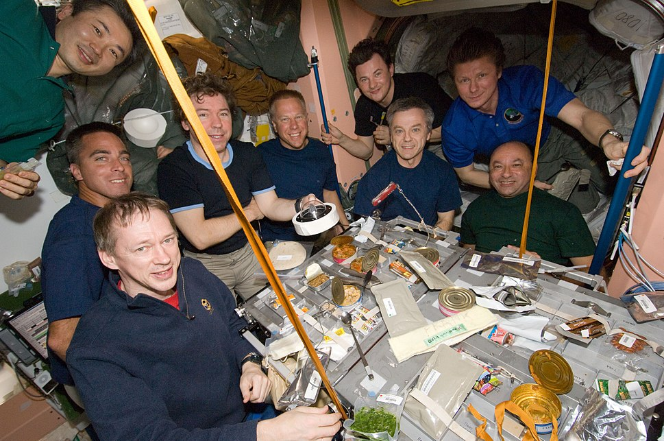 Nine astronauts seated around a table covered in open cans of food strapped down to the table. In the background a selection of equipment is visible, as well as the salmon-coloured walls of the Unity node.