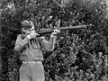 Military serviceman poses looking down the barrel of a rifle (AM 78402-1).jpg