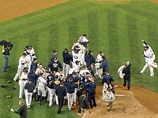 Many men in white baseball uniforms and blue caps, some wearing blue jackets, stand near a dirt mound. Some are hugging each other.