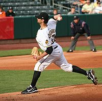 A side view of a young man in a baseball uniform, cap, and glove as he is about to throw a baseball off a pitcher's mound in a stadium. A uniformed umpire in the background looks on as the man has one foot nearly off the mound and the baseball behind his head.