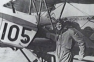 Pilot in flying gear next to biplane