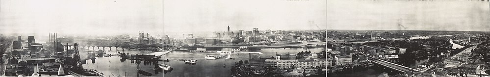 "Mississippi riverfront and Saint Anthony Falls in 1915. At left, Pillsbury, power plants and the Stone Arch Bridge. Today the Minnesota Historical Society's Mill City Museum is in the Washburn ""A"" Mill, across the river just to the left of the falls. At center left are Northwestern Consolidated mills. The tall building is Minneapolis City Hall. In the foreground to the right are Nicollet Island and the Hennepin Avenue Bridge."