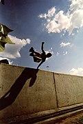 Un pratiquant de parkour au cours d'un saut « passement rapide » au-dessus d'un muret