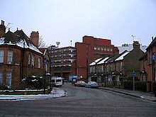 A tall red brick building towers over streets of two-storey houses. The roofs of the houses and the surrounding pavements are covered in snow