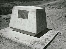 a black and white photograph of a concrete plinth with a plaque, overlooking a hill slope