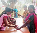 Polling official administering indelible ink to a voter at a pink booth, with all-women polling officials, at Malavalli, during the Karnataka Assembly Election, on May 12, 2018.JPG