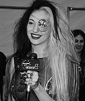A woman with long hair, half of it being blonde and the another half being dark wearing an eyepatch in her left eye talks to a microphone.