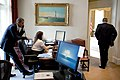 President Barack Obama talks on the phone with a Member of Congress, while Katie Johnson, the President's personal secretary, works at her desk in the Outer Oval Office.jpg