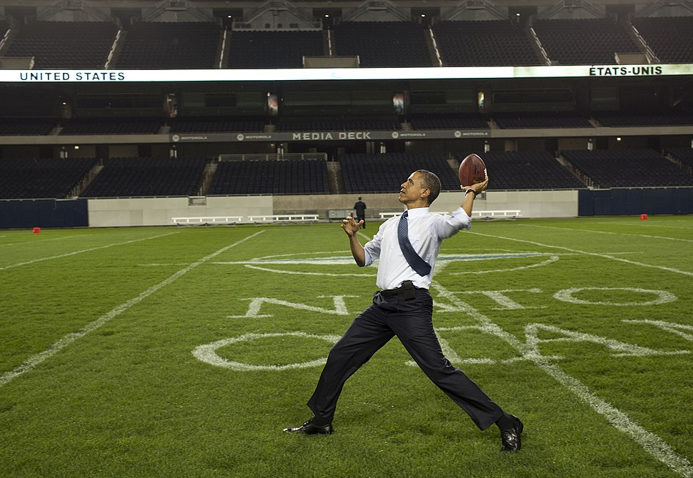 President Barack Obama throws a football