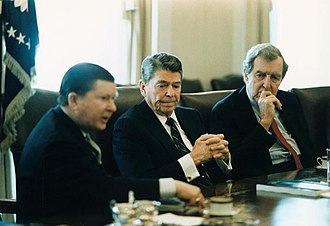 Iran–Contra affair - President Reagan (center) receives the Tower Commission Report in the White House Cabinet Room; John Tower is at left and Edmund Muskie is at right, 1987.