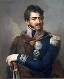 Color portrait of a man with dark brown hair, mutton chops and a moustache. He wears a dark blue uniform with silver braid and a fur cape over his right side.