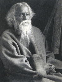 Late-middle-aged bearded man in Grey robes sitting on a chair looks to the ight with serene composure.