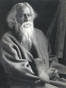 Late-middle-aged bearded man in Grey robes sitting on a chair looks to the right with serene composure.