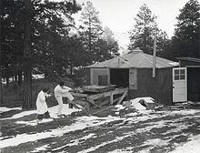 Eine Hütte, umgeben von Kiefern.  Es liegt Schnee auf dem Boden.  Ein Mann und eine Frau in weißen Laborkitteln ziehen an einem Seil, das an einem kleinen Wagen auf einer Holzplattform befestigt ist.  Auf dem Wagen befindet sich ein großes zylindrisches Objekt.