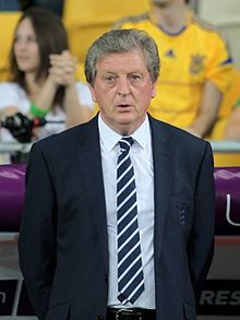 A photograph of a grey-haired, middle-aged man at a football match. He is wearing a black suit, a white shirt and a black and white striped tie. He is watching the game from the sideline.