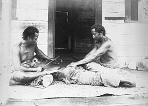 Pe'a - Tattooist, tufuga ta tatau, (left) and assistant (right) tattooing a man's back, c 1895, photo by Thomas Andrew