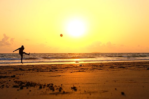 Silhouette kicking the ball at the beach (Unsplash).jpg