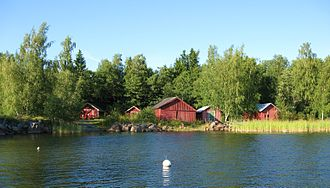 Korsholm - Falu red boathouses in Grönvik, a typical scenery in coastal Korsholm. Rugged glacial stones washed by the sea armor the gently sloping shore forested with silver birch.