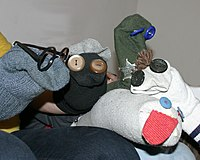 A number of literal sock puppets with buttons for eyes. One wears a pair of glasses. Another has yarn for hair.