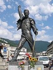 Statue noire photographiée de face, représentant un homme aux cheveux courts qui observe vers le bas, tenant un pied de micro dans sa main gauche et levant son poing droit.