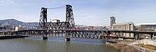 Le pont Steel Bridge est marqué par deux tours de fer qui maintiennent le pont, lui-même en fer. La rivière Willamette passe dessous. Des deux côtés du pont, quelques bâtiments de Portland apparaissent.