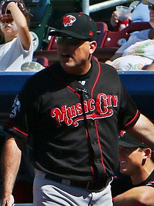 "A man in a black baseball jersey with red trim and ""Music City"" written in red letters across the chest, a black cap with an ""MC"" on the front, and gray pants stands in front of a dugout."
