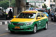 """A Toyota saloon/sedan driving on the road, its top half painted in yellow and the bottom half in green, with a sign on the roof saying """"TAXI-METER"""" and a yellow licence plate"""