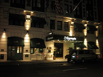 Spotlights accentuate the hotel's stone facade and arched store windows with awnings. A large awning covers the entrance to the hotel.