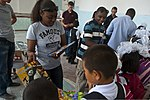 U.S. Air Force Staff Sgt. Barbara Case, left, a noncommissioned officer in charge of material control, and Airman 1st Class Lavandis Acklin, a fuel distribution journeyman, hand out coloring books to students 120903-F-KX404-044.jpg