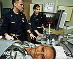 U.S. Navy Lt. Tyler Vachon, left, and Cmdr. Danielle Taysom look at the ultrasound of a mass on the right arm of an Indonesian man in the radiology room aboard Military Sealift Command hospital ship USNS Mercy 120602-O-ZZ999-013.jpg