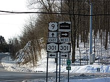 A series of road signs in front of an intersection between two highways. The hill behind the intersection is covered in snow; electrical wires hang overhead.