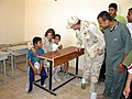 US Navy 030424-M-8658H-003 Rear Adm. Charles Kubik, Commander, First Naval Construction Division, speaks to two Iraqi boys about the new Umm Qasr High School just reopened, with the assistance of a translator.jpg
