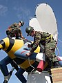 US Navy 041211-N-1594R-003 Construction Electrician Constructionman Thiago DeToledo, left, assists Construction Electrician Constructionman James Mason, in wrapping a giant Seabee statue with Christmas lights.jpg