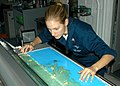 US Navy 050903-N-2699R-001 Photographer's Mate 2nd Class Nichole Dinda of Rock Creek, Ohio, guides a map of the Gulf Coast area into a laminator in the print shop aboard the Nimitz-class aircraft carrier USS Harry S. Truman (CV.jpg